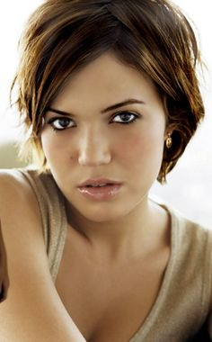 mandy moore short hair This simple short haircut is parted in a zigzag and enhanced with a sexy somewhat messy finish that is currently in the mainstream. The golden highlights enliven the whole look.