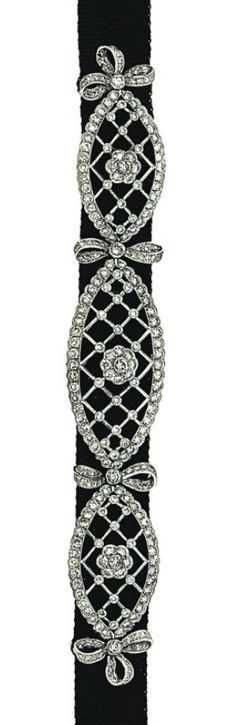 A diamond-set choker   Composed of three graduated panels set on a black ribbon choker, each oval openwork plaque with brilliant-cut diamond borders and details, to a brilliant-cut diamond flowerhead centre and bow-shaped connecting links, the clasp of similar design, 35.0cm long. Edwardian or Edwardian style.