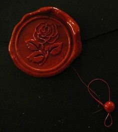 The seal on the envelope is red wax, with a rose design… interesting.