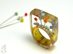 Sewing basket - extraordinary sewing supplies ring with measuring tape, colourful fixing pins and snap fastener on a yellow resin ring