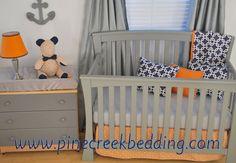 Nautical boy's nursery with navy, orange and grey crib bedding