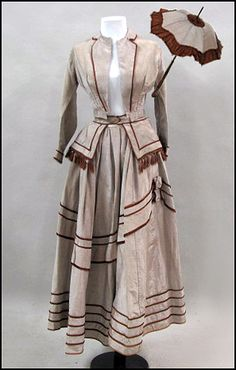 BEIGE SILK DRESS WITH BROWN SATIN TRIM Together with matching parasol. Circa 1870