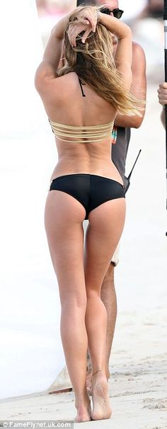 Life's a peach: Candice displayed her pert bottom as she frolicked in the sand for the photographer