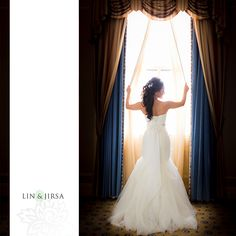 love this shot of the back of the gown with the bride holding the curtains