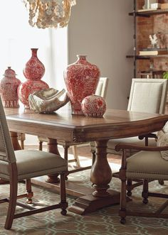 Fit for a simple rustic meal, or a king's feast, the unique 3-pillar Tennyson Trestle Table is built from solid, carved and distressed wood. The reclaimed look is further detailed with carved sunbursts at the four corners. The linen upholstered Tennyson Arm and Side Chairs tuck neatly under its impressive length.