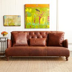 """ALCAZAR LEATHER SOFA--Burnished terracotta leather, lightly distressed to suggest generations of sprawling comfort, shapes a sofa with considerable presence. Curving arms and a tight bench seat complement the lavishly diamond tufted back with nailhead detail. We''re including one lumbar and two throw pillows. Crafted in the USA with FSC-Certified maple frame, webbed support and turned wood legs. 72""""W x 42""""D x 32""""H."""