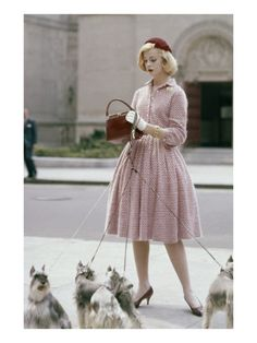 Glamour - October 1959 by Sante Forlano. Model with dogs on leash, wearing knitted dress by Anne Fogarty , velvet hat by Emme, and alligator bag by Lucille.