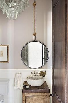 Perfectly polished rustic. The rope hanging the round mirror over the tiny sink makes this bathroom!