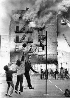 Children playing basketball next to a burning building in Harlem, New York City, 1975. @historylvrsclub