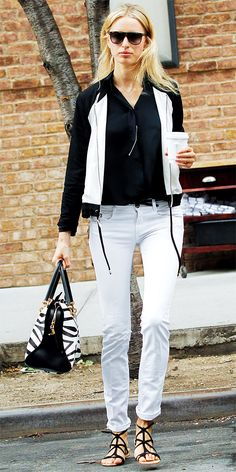 Karolina Kurkova in a black-and-white outfit, styling her white skinnies with a black top, zebra-print Tod's bag and black strappy sandals.