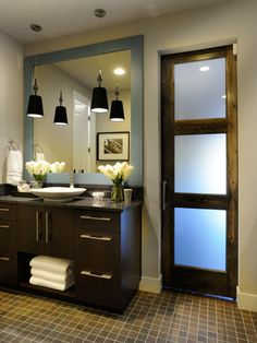 The clean lines and dark neutral color scheme of this contemporary bathroom are complemented by a rough-hewn wood and glass door.
