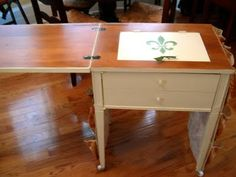 old sewing table repurposed: added wheels and covered the machine opening with a hinged cover for storage beneath and a larger tabletop for working