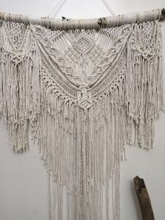 This large boho macrame wall hanging will transform your space. Its extremely detailed and intricate, made with layers upon layers of meticulously hand-knotted natural cotton twine and comes mounted on a sealed birch branch that has been kiln heated for sanitation. There are slight variations in each wall hanging -- each one is made to order and is a one-off of the one you see pictured.  Size is approx 27 inches wide x 34 inches long. Please allow approximately 6 weeks to ship and 2-3 days…