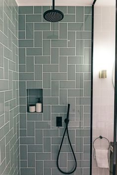 Contemporary bathroom with black faucets tiles in a herringbone pattern. Rain and hand shower and built-in niche for your shower supplies. Design and production of a dream bathroom on the Bilderdijkkade in Amsterdam. We mixed vintage and modern elements