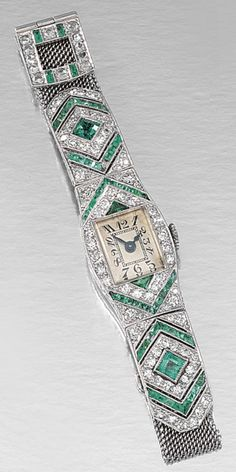 LADY'S EMERALD AND DIAMOND DRESS WATCH, 1920S.  The rectangular face applied with Arabic numerals and blued steel hands, the tonneau-shaped dial, arranged with chevrons of circular- and single-cut diamonds with French-, step-cut and triangular emeralds, to a fine mesh bracelet strap, with a rose-cut diamond and French-cut emerald fastening, length approximately  145mm to 215mm adjustable.