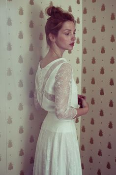 Beautifully soft in white and lace ... red head stands against vintage wall paper.