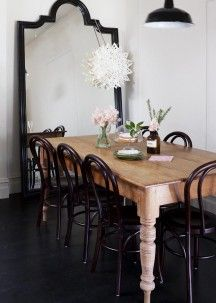 Chic dining room with black arched floor mirror at the end of the space reflecting the black enamel pendant hung over a rustic farmhouse dining table lined with Thonet Bentwood chairs atop black hardwood floors. Table And Chairs, Dining Chairs, Room Chairs, Table Legs, Office Chairs, Dining Set, Sala Grande, Bentwood Chairs, Metal Chairs