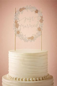"""This unique and romantic """"Just Married"""" Cake Topper has lasercut swirling vines and pale pink flowers, $28, BHLDN"""
