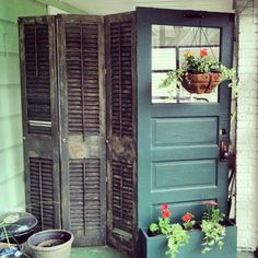 Scored old door free in an alley.  Repurposed it by adding flower box and shutters to create a privacy divider for duplex with shared screened in patio