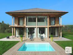 Maison reliée directement à une piscine extérieure grâce à une terrasse en lame de bois. Au centre de cette terrasse se trouve une piscine carrée composée de quelques escaliers.