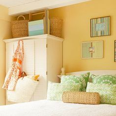 Sail away to your very own beach house haven by combining airy blues, greens, and yellows. A crisp white duvet and armoire stand out against the light yellow walls. Several wicker beach baskets and a montage of beach memories in distressed frames contribute to the casual summer feel of the room.