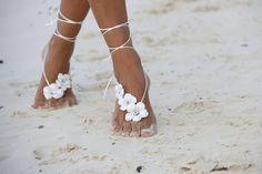 Mariée sur le sable avec des pieds ornées de fleurs, magnifiques !