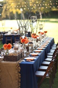 This looks so good because blue and orange are complementary colors and because of a contrast of texture with the burlap. Orange flowers pop on navy tablecloths