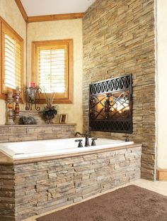 Cultured stone on tub and back wall.  Solid (granite? not sure the material) tub surround and step.