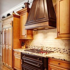 "Patricia Presto of On the Surface says, ""No need to paint ALL your cabinetry...we added ""pieces of jewelry"" in this grand kitchen by painting jet black on hood & lower cabinets, glazed for sparkle w/copper & bronze, added a ""faux"" copper strip created w/foils and glazes. Now we have a focal point, while also adding my client's love for antique copper to this beautiful space!"" 