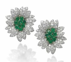 A PAIR OF EMERALD AND DIAMOND EAR CLIPS, BY VAN CLEEF & ARPELS   Each modelled as a flowerhead with circular-cut emerald pistil extending pavé-set diamond petals, 4.0 cm, with French assay mark for gold, in grey suede fitted Van Cleef & Arpels case  Signed Van Cleef & Arpels