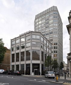 """the economist building, london 1959-1964. architects: peter and alison smithson (1923-2003 & 1928-1993).  the bank building in front of the economist tower as seen from st. james' street. took me a while to realize the fire wall on the left is also by the smithsons, I have to admit.  this photo was uploaded with a CC license and may be used free of charge and in any way you see fit.  if possible, please name photographer """"SEIER+SEIER"""". if not, don't.  the smithsons."""