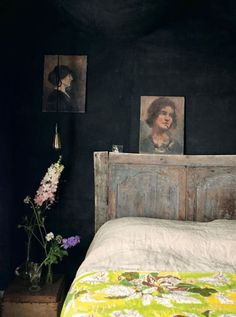 Dark walls, oil portraits, flowers on a dark background, old wooden headboard, floral bedspread