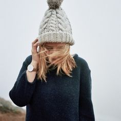 Black knit jumper, grey chunky knit bobble hat, brown strap white faced watch