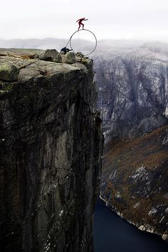 Eskil Rønningsbakken balancing on a thin, yet huge wheel on the very edge of Kjerag, which is an approximatly 1 km dive (if he falls) right into the ocean