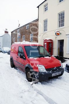 It's Christmas the Mail MUST Get Through. Red Royal Mail Post Van----A Royal Mail Van outside a village Post Office in the snow, Wrington, Somerset, England, United Kingdom