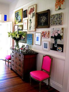Foyer Hall. Love the wall art and that POP of PINK of the chairs. Somehow, it works.