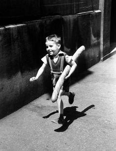 """Le petit parisien-Fotografia feita em 1952 e considerada uma das mais importantes do fotógrafo francês Willy Ronis. Intitulada """"Le petit parisien"""", mostra um garoto parisiense que corre levando debaixo do braço uma baguete maior do que ele. A fotografia percorreu o mundo como marca da Paris no pós-guerra. Fotografia: Willy Ronis"""