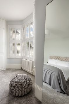 The muted grey tones in this bedroom look extremely luxurious and create a classic look and a very cosy bedroom. The period feature fireplace contrasts this and the bay window shutters complete the look.   #interiordesign #interiorarchitecture #architecture #design #industrialdesign #homedecor #home #bedroomdesign #interiordesigner #interiors123 #project #london #shutters #plantationshuttersltd #bespoke #madetomeasure #windows #decor #decoration #relax #trending #inspiration