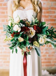 red flower bouquet with greenery - photo by Jessica Gold Photography http://ruffledblog.com/dusty-blue-and-cranberry-wedding-inspiration