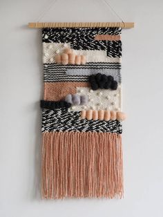Woven boho wall hanging centered on a wooden dowel and finished with a cord for hanging. The tapestry is in beige, pink, white, grey and black color. This piece is totally unique and made with lots of love. It will definitely add some happy boho style to your home!  SIZE: Width: 25 cm