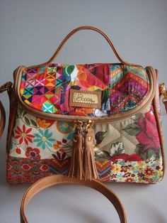 Bolsa feita de tecido de algodão quiltada, detalhes e alça de couro ecológico.