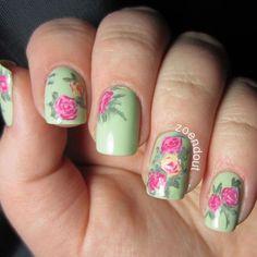 Hermosa manicura de uñas en verde pastel adornadas con diseños de flores rosas con hojas.