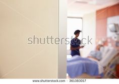 Focus On Hospital Room Sign With Nurse Talking To Patient - stock photo