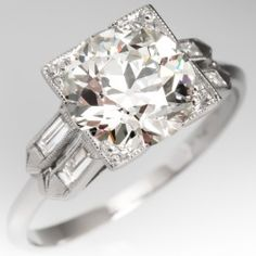 This stunning vintage engagement ring features a 2.37 carat old European cut center diamond with the most amazing sparkle. The ring is crafted of platinum and set with two baguette diamonds on each side with details and milgrain edging.