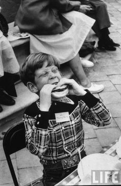 Timmy Garry, dressed in cowboy outfit, ferociously biting into his hamburger at a Hollywood children's party. 1952. By J. R. Eyerman