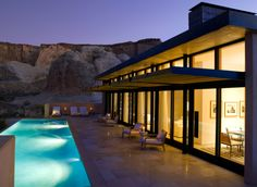 This ultra-modern home in the desert has tile flooring, clean lines, a cantilevered overhang,walls of glass, high ceilings, a massive chimney and linear pool.