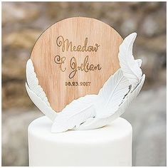 Pour une decoration de gateau de mariage rustique, ce sujet composé de plumes et de bois completera votre decor de gateau