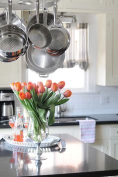i don't know if it's the #flowers or hanging cookware but i'm smitten. #kitchen #whitecabinets