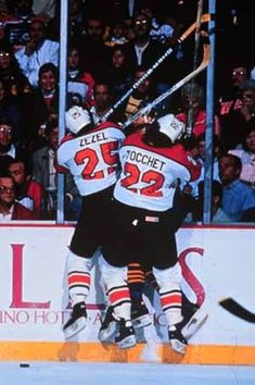 Flyers Peter Zezel and Rick Tocchet check an opponent into the boards.