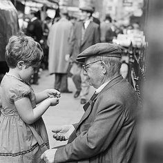 Caption: A young girl and a man wearing a flat cap in Petticoat Lane Market Photographer: John Gay Date Taken: 1957 - 1962 Vintage London, Old London, East London, Monochrome Photography, Street Photography, London Market, London History, London Pictures, English Heritage